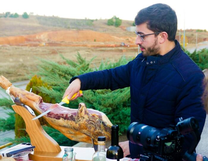 David González, CEO de Iberic Box cortando jamón. Momento de la grabación del vídeo en el que la cámara aparece en el margen inferior derecho. En primer plano, David González, cortando un jamón que está en un jamonero en una mesa situada en el exterior. El fondo son campos.