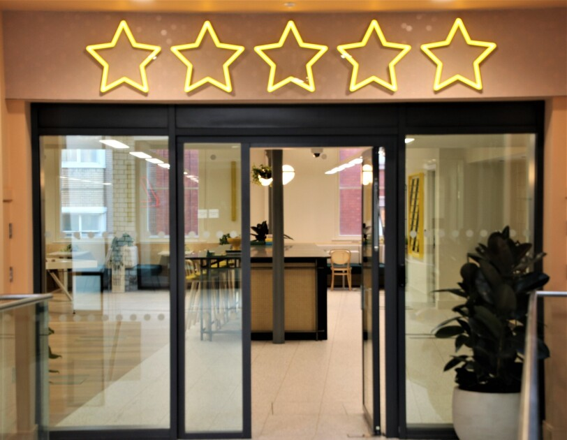 A view of the break area in the Amazon Manchester offices, this is viewed from outside of the open doors. Above the doors are neon lights depicting five stars.