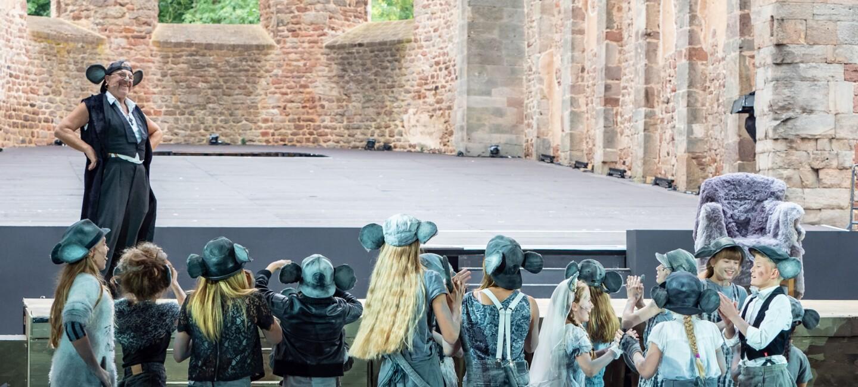 In der historischen Stiftsruine Bad Hersfeld ist eine große Bühne aufgebaut, im Hintergrund sieht man Mauerwerk in Backsteinen und glaslose Fenster der ehemaligen Stiftsruine. Auf der Bühne ein Schauspieler im Mäusekostüm. Vor ihm stehen ca. ein Dutzend Kinder, ebenfalls in Mäusekostümen.