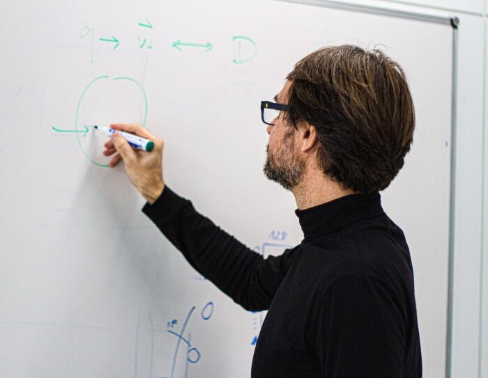 Hugo Zaragoza es investigador en el equipo Subjective NLP (Natural Language Processing) en Amazon Search. En una pizarra de pared Hugo está escribiendo con un rotulador verde. El lleva gafas, barba de una semana de color negra y blanca. Pelo por las orejas y jerseu negro de cuello alto.