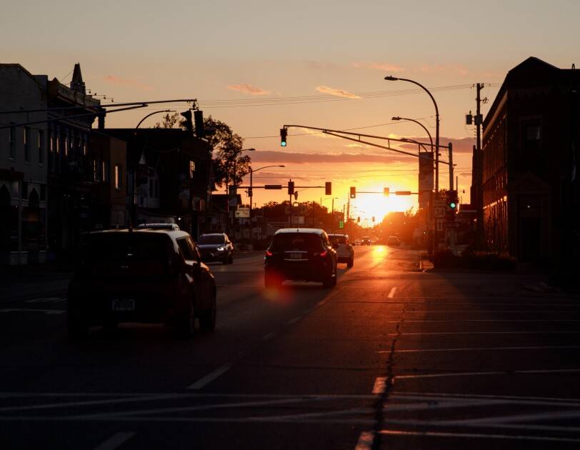 The sun dips below the horizon. In the foreground, a small town commercial district is shown in shadow.