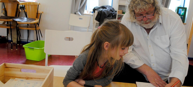 Buchkinder-Gründer Rulo Lange ist rechts neben einem etwas sechsjährigen Mädchen zu sehen. Er erklärt ihr etwas, das auf einem Blatt vor ihm zu sehen ist.