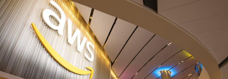 Edificio_AWS. Entrada al edificio de AWS de Amazon. En la entrada con el suelo gris y rombos de color rojo, naranja y amarill. Hay cuatro escaleras automáticas y unas escaleras en medio. El texto es blanco y en una columna del fondo hay luz indirecta azul. Hay gente subiendo y bajando pero difuminada.