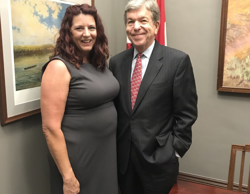On the left, a female (Kindle Direct Publishing author, Denise Grover Swank) in a dark gray dress stands next to a man (Senator Roy Blunt) wearing a suit.