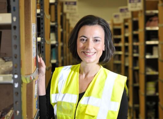 Eine Frau mit halblangem Pagenschnitt und braunen Haaren lehnt leicht an ein Regal eines Logistikzentrums. Sie trägt eine gelb-blaue Sicherheitsweste.