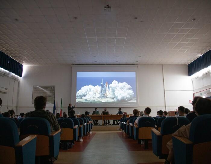 Sala riunione all'interno del magazzino di Colleferro di Amazon. In fondo, in mezzo alla platea di sedie è appeso sul muro un telo per proiettore sul quale si vede l'immagine di un razzo spaziale in procinto di decollare. In platea, un gruppo di studenti ripresi di spalle