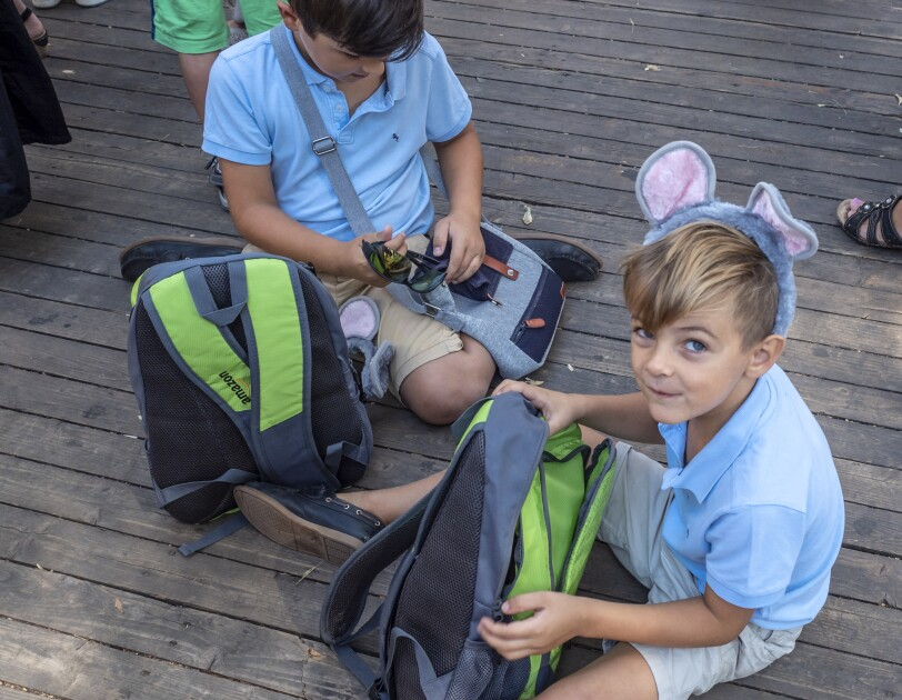Zwei Kinder sitzen am Boden. Beide tragen einen Haarreif mit Mäuseohren. Vor ihnen der Rucksack von Amazon, den jeder der kleinen Gäste erhalten hat.