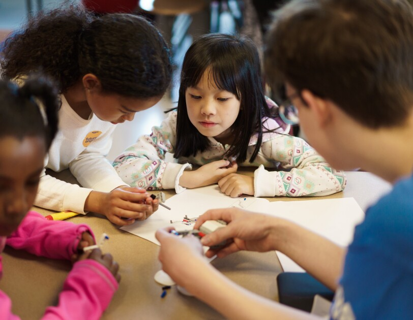 Children sit at a table and assemble a STEM toy.