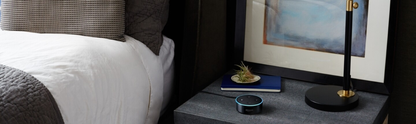 A black Amazon Echo Dot on a black nightstand.
