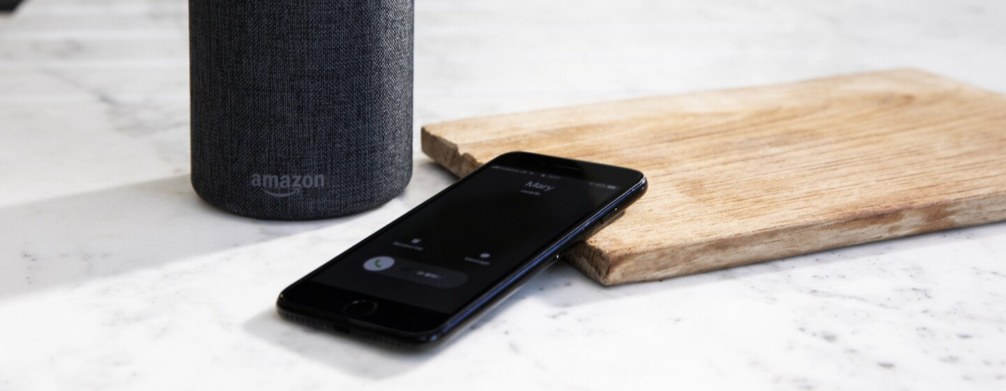 An Amazon Echo sits on a kitchen counter, in front of it, a cellular phone rests against a cutting board.