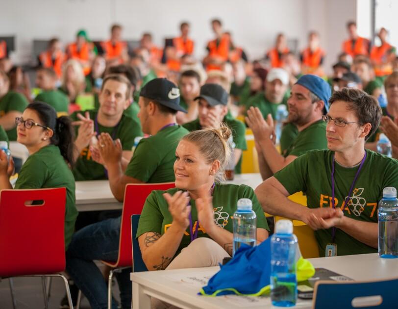 """Mitarbeiter, alle in grünen T-Shirts mit """"FRA7""""-Aufdruck, sitzen an langen Tischreihen in der Kantine. Man sieht lächelnde Gesichter. Alle Mitarbeiter klatschen."""