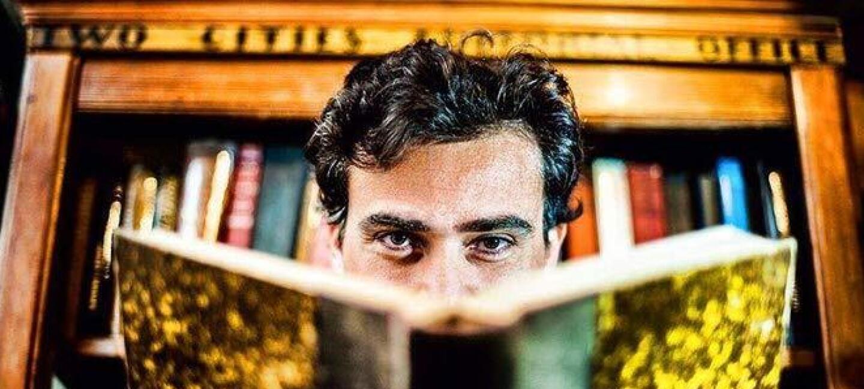 L'auteur Gregory Samak lit un livre relié qui cache la moitié basse de son visage. Derrière lui se tient une bibliothèque remplie de livres.