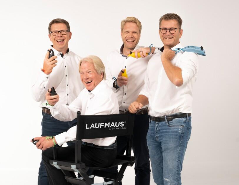 Vier Männer in weißen Hemden halten Laufmäuse in den Händen und lachen in die Kamera.