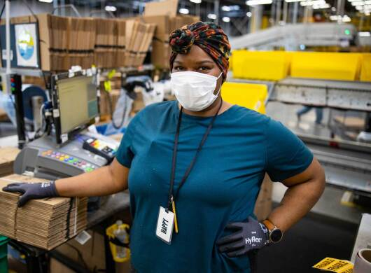 An Amazon associate working at a fulfillment center pack station poses for the camera while wearing a protective surgical mask