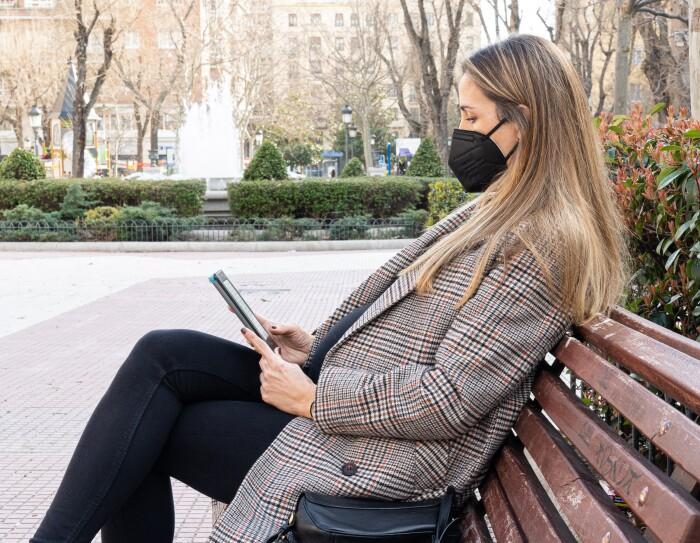 Silvia Cubero, Deals Program Manager Amazon Marketplace. En un banco marrón de madera de un parque que de fondo tiene una fuente en una glorieta. Silvia con una barriga de nueve meses está leyendo en un Kindle. Tiene el pelo largo y va con mechas rubias. Lleva unos pantalones y un jersey negros, un abrigo de cuadros y una mascarilla negra.