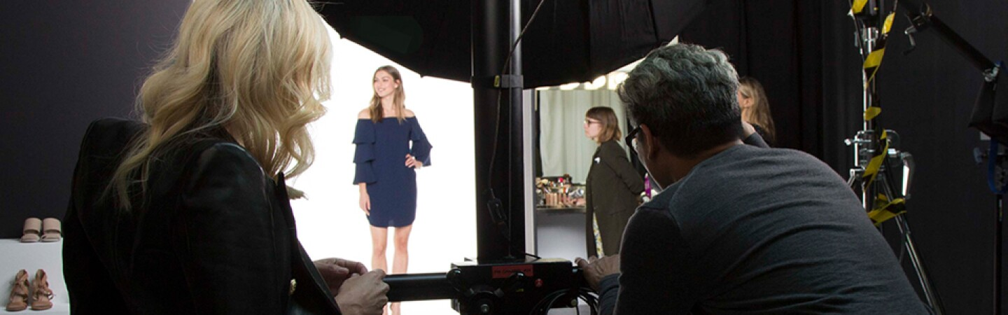 Two individuals, a male photographer and a woman in a leopard-print dress and dark jacket draped over her shoulders, photograph a model wearing a blue dress during an Amazon Fashion shoot.
