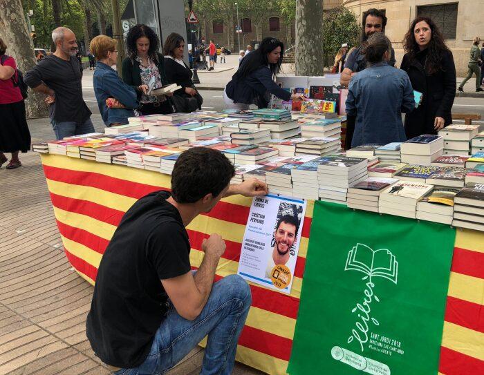Cristian Perfumo, el escritor de la Patagonia, está de rodillas enganchando un cartel promocional de la firma de sus libros para Sant Jordi en una mesa llena de libros también suyos.