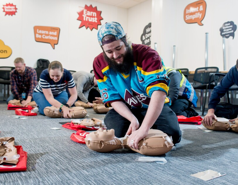 Amazon Operations Supervisor Lloyd Curley kneeling on the floor and practicing CPR on a dummy, along with five of his colleagues doing the same in the background.