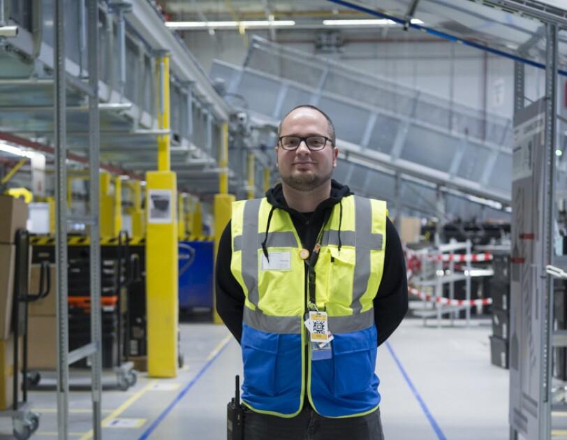 Ein Mann in schwarzer Jeans und gelb-blauer Sicherheitsweste steht breitbeinig in einer Lagerhalle. Er trägt Bart und Brille.