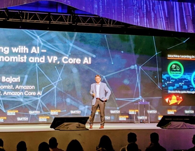 """A man stands on stage at a conference, presenting on """"Innovating with AI"""""""