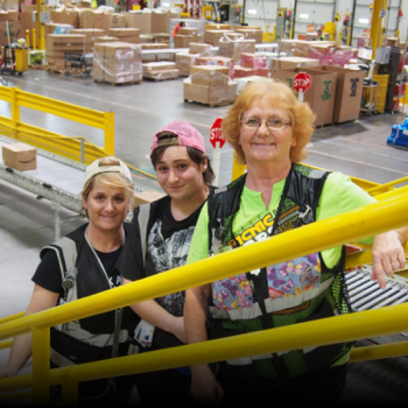 Three generations of a family who work together at an Amazon fulfillment center, pose together at their workplace.