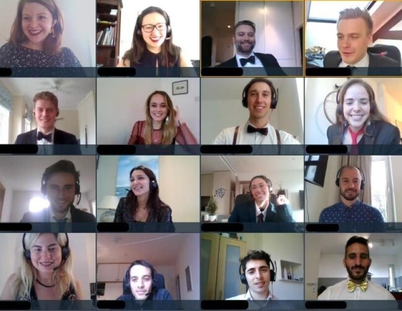 Männer und Frauen mit Headsets in einer Videokonferenz lachen in die Kamera.