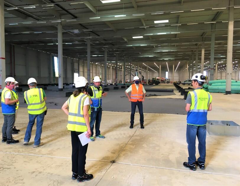 Eine Gruppe von Besuchern in der neuen Logistikhalle.