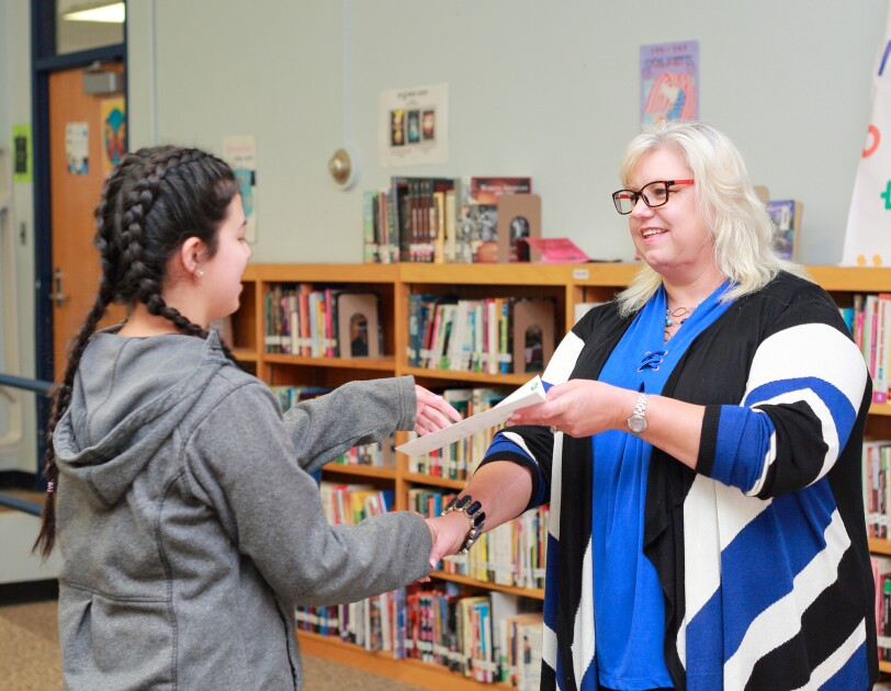 A high school student shakes the hand of a woman standing in front of her in a school library. The woman is simultaneously handing the student a document.
