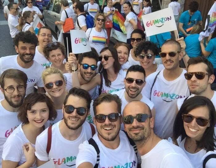 Gruppo di dipendenti Amazon in posa al Pride di Milano. Indossano una t-shirt con la scritta 'Glamazon' e molti di loro hanno gli occhiali da sole.