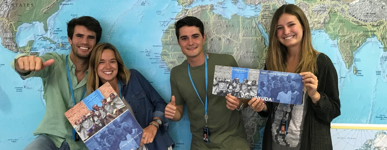 Delante del mapa del mundo, cuatro amazonians, se muestran en actitud informal: dos mujeres con folletos de la iniciativa solidaria para la que están trabajando y los dos hombres haciendo la señal de OK a cámara.