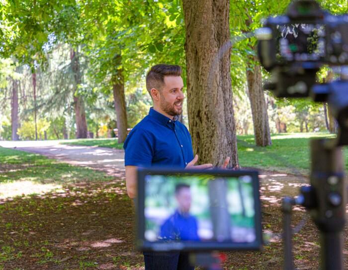 Paul Pen en un momento de la grabación de la historia en el Parque de El Retiro (Madrid). En primer plano sale la cámara con la pantalla y el protagonista desenfocado. En segundo plano pero enfocado está Paul Pen hablando a cámara. Lleva una camisa azul y unos pantalones tejanos. De fondo se ven los árboles del parque.