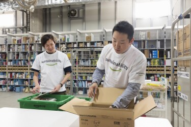 Two Amazon employees wearing 'sustainability' t-shirts work to pack a box together.