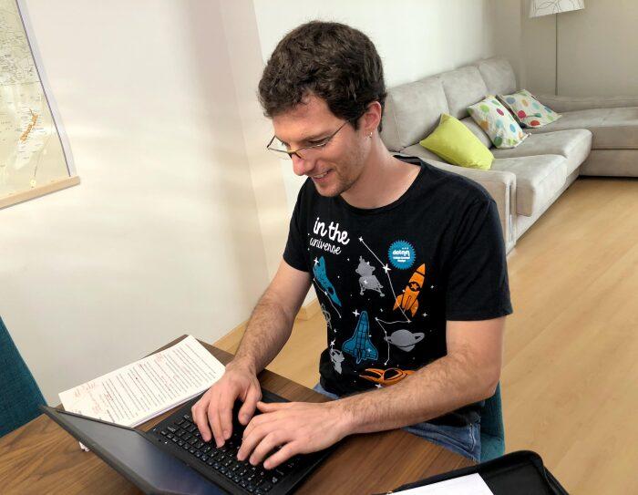 Cristian Perfumo, el escritor de la Patagonia, está sentado en una mesa de comedor y trabajando en su ordenador. Viste una camiseta deportiva y en la mesa tiene unas hojas de papel con correcciones en color rojo.