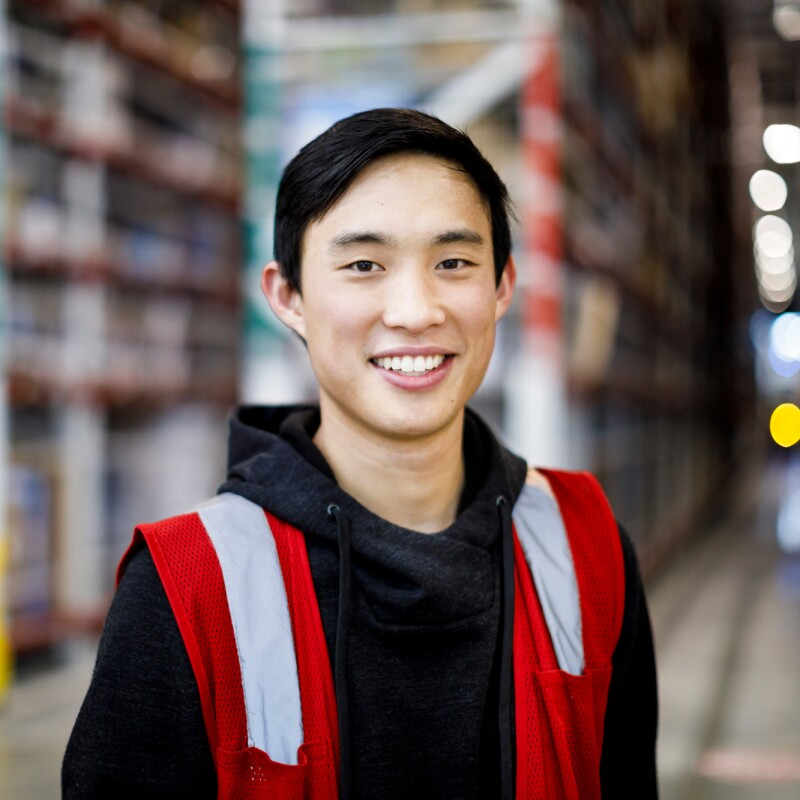 Amazon Military Leaders Program member Julius Yu looks into the camera at an Amazon warehouse, or Fulfillment Center. He is wearing an orange safety vest.