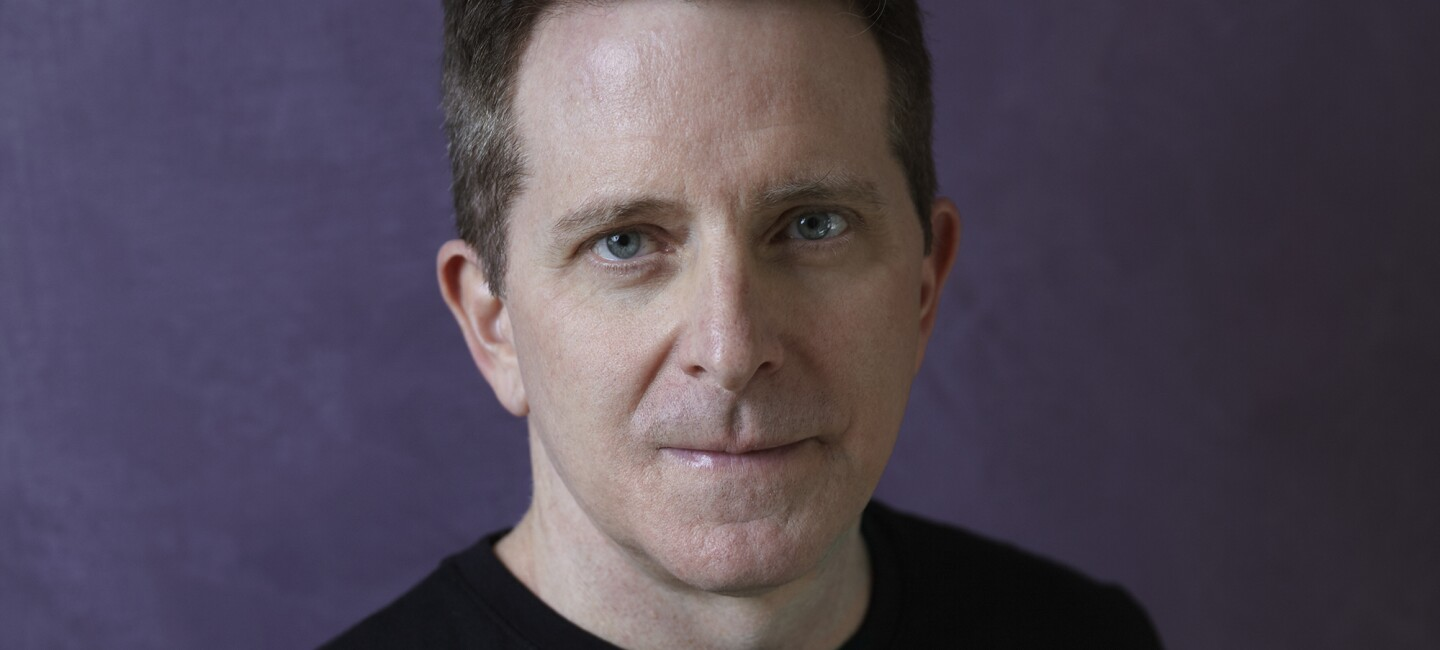 Amazon author Landon J. Napoleon stares into the camera. He has dark hair, blue eyes, and is wearing a black sweater. The background is purple.