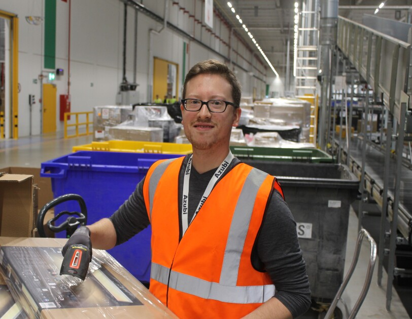 Ein Mann mit braunen Haaren und Brille: Er trägt eine orange-farbene Sicherheitsweste und scannt gerade ein Paket.