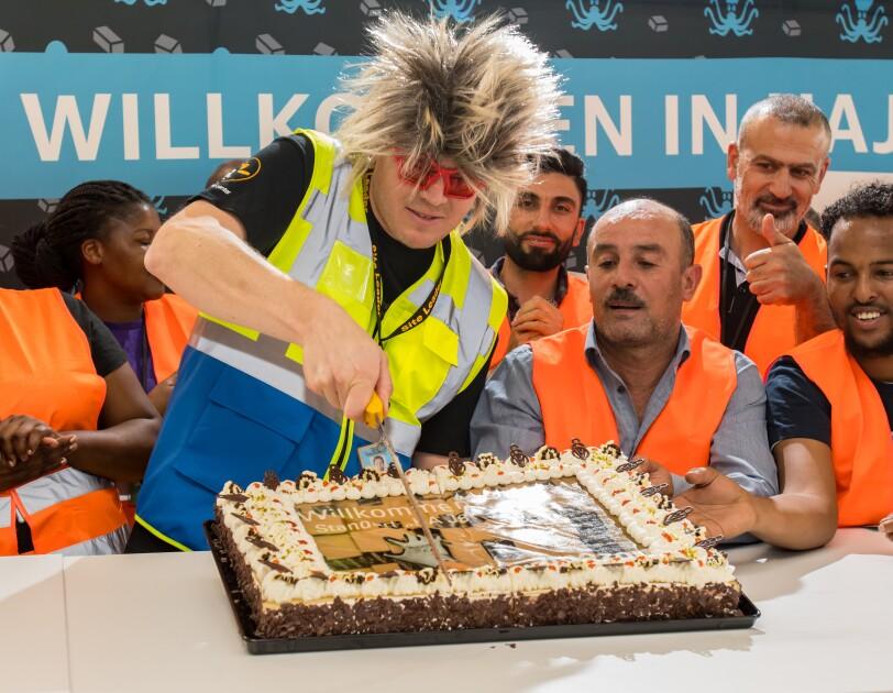 Ein Mann mit Igelperücke und roter Spaßbrille, von Logistikmitarbeitern umgeben, schneidet eine rechteckige Torte an