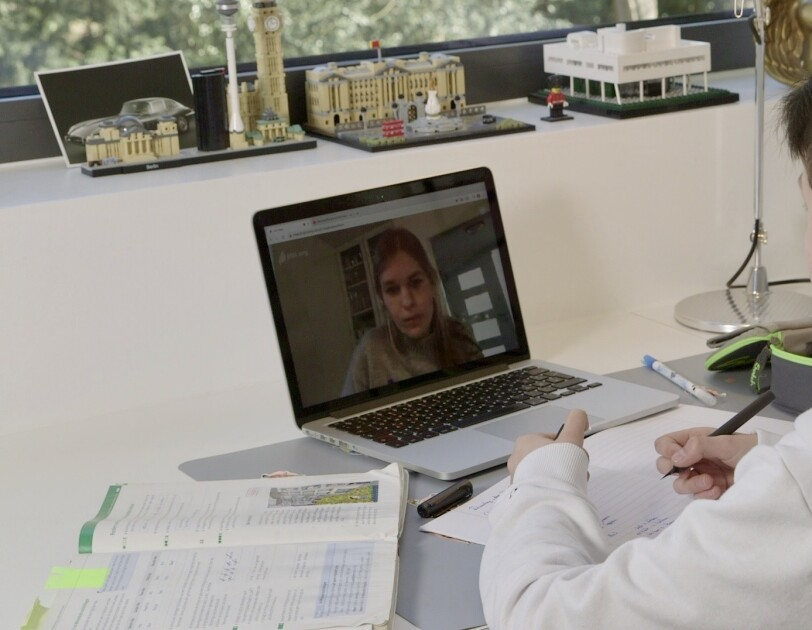 Ein Junge schaut auf einen Laptop. Auf dem Laptopbild ist eine junge Frau mit blonden Haaren zu sehen.