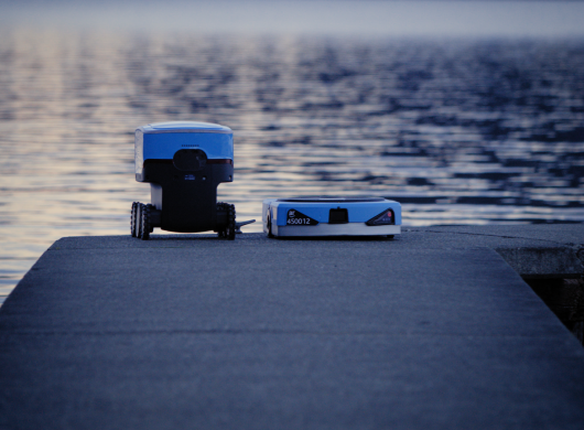 An Amazon Scout delivery robot sits on a pier, next to a Kiva robot.
