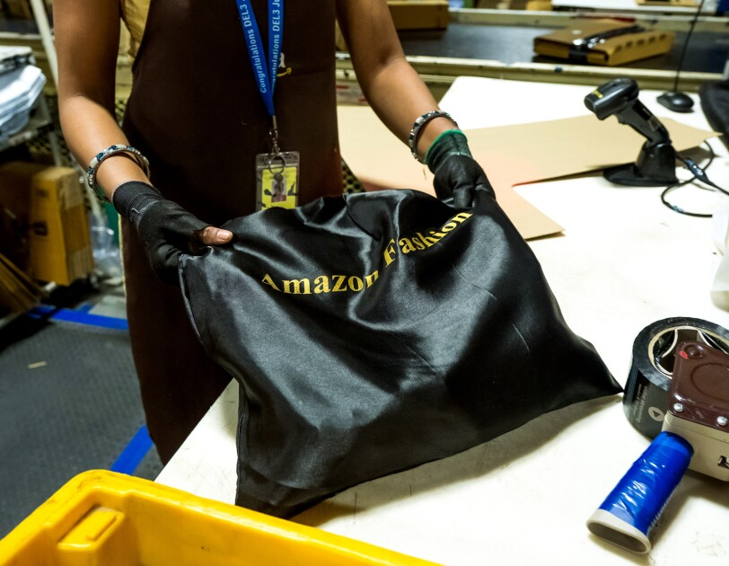 """A person photographed from the torso down holds a black satin bag labeled with the words """"Amazon Fashion."""" The image also contains packing tape and a scanner. Boxes move along a conveyor belt in the background."""