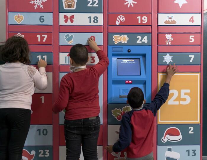 Locker Amazon ricoperto da adesivi natalizi su fondo rosso. Di fronte al Locker giocano 3 bambini, ripresi di spalle.