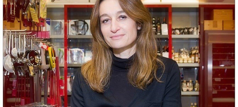 Valérie Le Guern Gilbert se tient devant des vitrines et des présentoirs où sont rangés des ustensiles de cuisine : passoires, râpes, carafes...