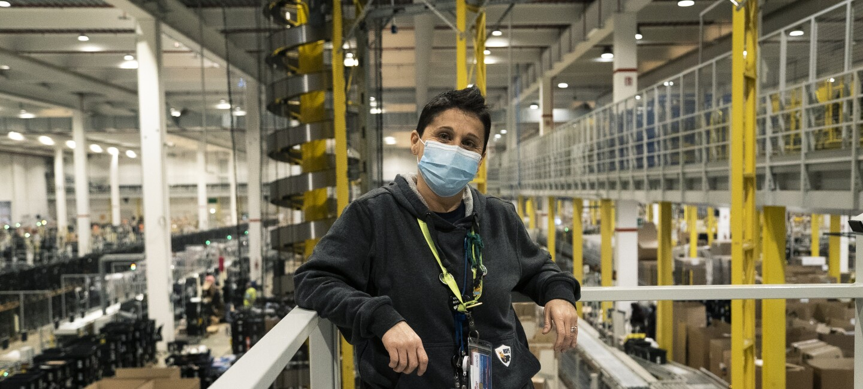 Una donna con i capelli corti indossa una mascherina chirurgica sul volto e poggia i gomiti su una balaustra alle sue spalle. Sullo sfondo di vede l'interno di un magazzino Amazon.