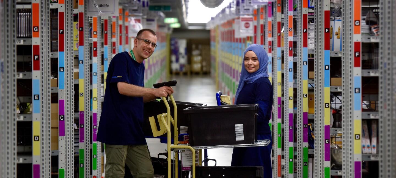 Ein männlicher und ein weiblicher Logistikmitarbeiter (letztere mit Kopftuch) sind zwischen den Regalreihen eines Logistikzentrum zu sehen