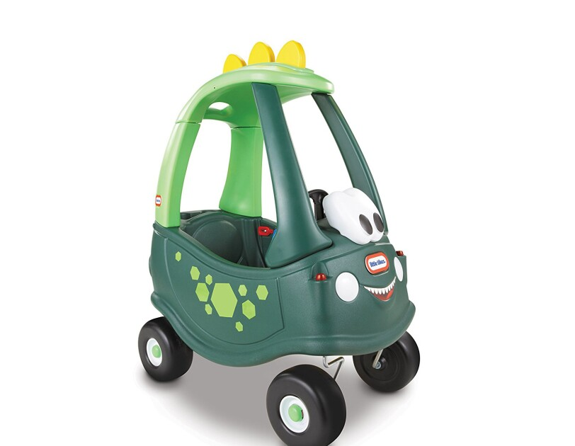 A Little Tikes Cozy Coupe children's ride-on car, in an exclusive dinosaur design, with a dino spine on the roof, green body, and large eyes.