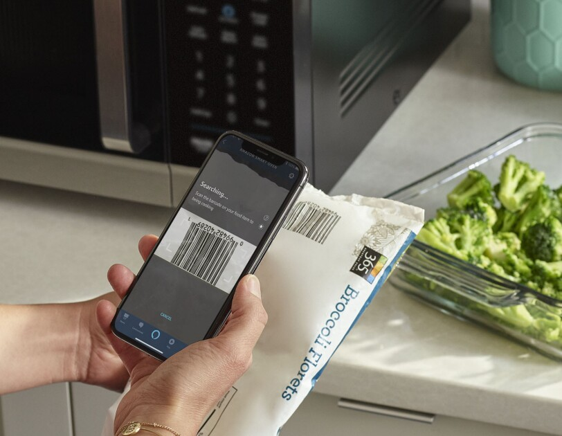 A person holds a package of 365 frozen broccoli florets, scanning the bar code on their phone to get cooking instructions.