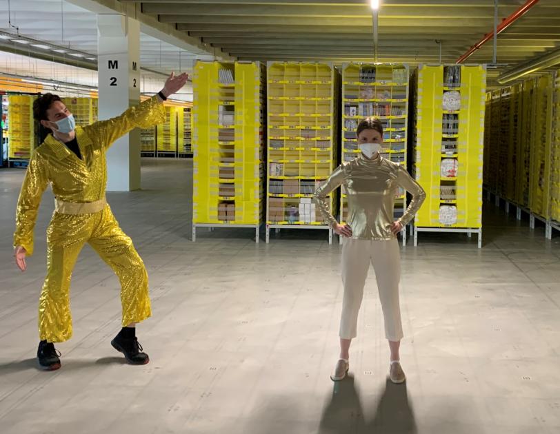 Drei Mitarbeiter:innen aus dem Logistikzentrum in Sülzetal in goldenen Anzügen.