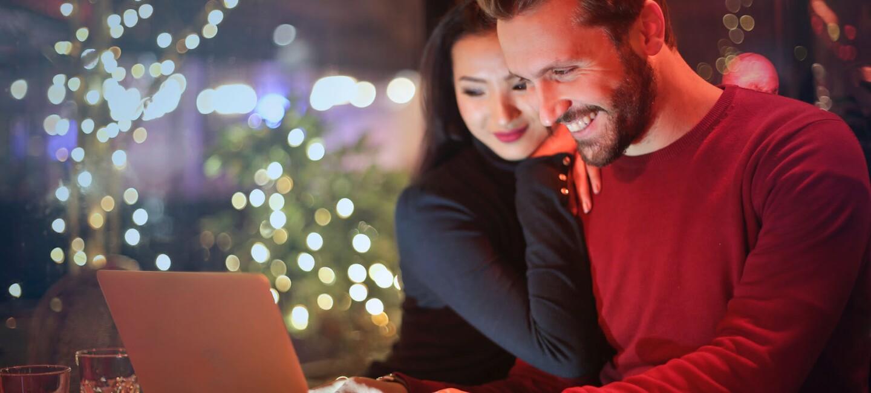 Ein Pärchen sitzt gemeinsam vor dem Laptop. Im Hintergrund sieht man weihnachtliche Dekoration, Lichterketteun, Tannenbäume.