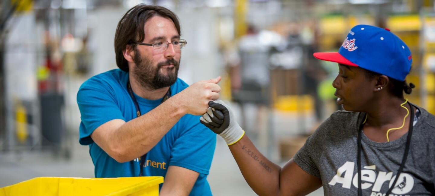 An male Amazon associate in a blue t-shirt bumps fists with a female Amazon associate wearing a grey t-shirt that says 'Aeropostale'. Three yellow bins are in front of the man, and the woman is wearing a blue baseball cap.