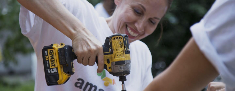 Volontaria di Amazon sorride in primo piano mentre regge un trapano durante i lavori alla Scuola Media Leonardo da Vinci di Affori, nella periferia di Milano.